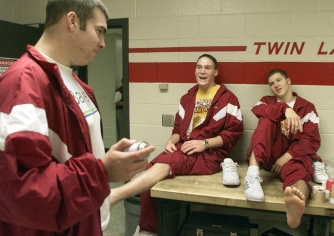Scott Anderson (left), Brandon Lancaster (center) and Kevin Downham share a laugh before getting their ankles taped at Twin Lakes High School.