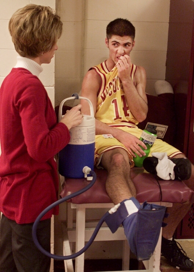 Bart Hunsicker listens to athletic trainer Alicia Clevenger after turning his ankle during the home game against Rensselaer early in the season. The cryo-cuff on his foot is filled with cold water and is used to help control swelling.
